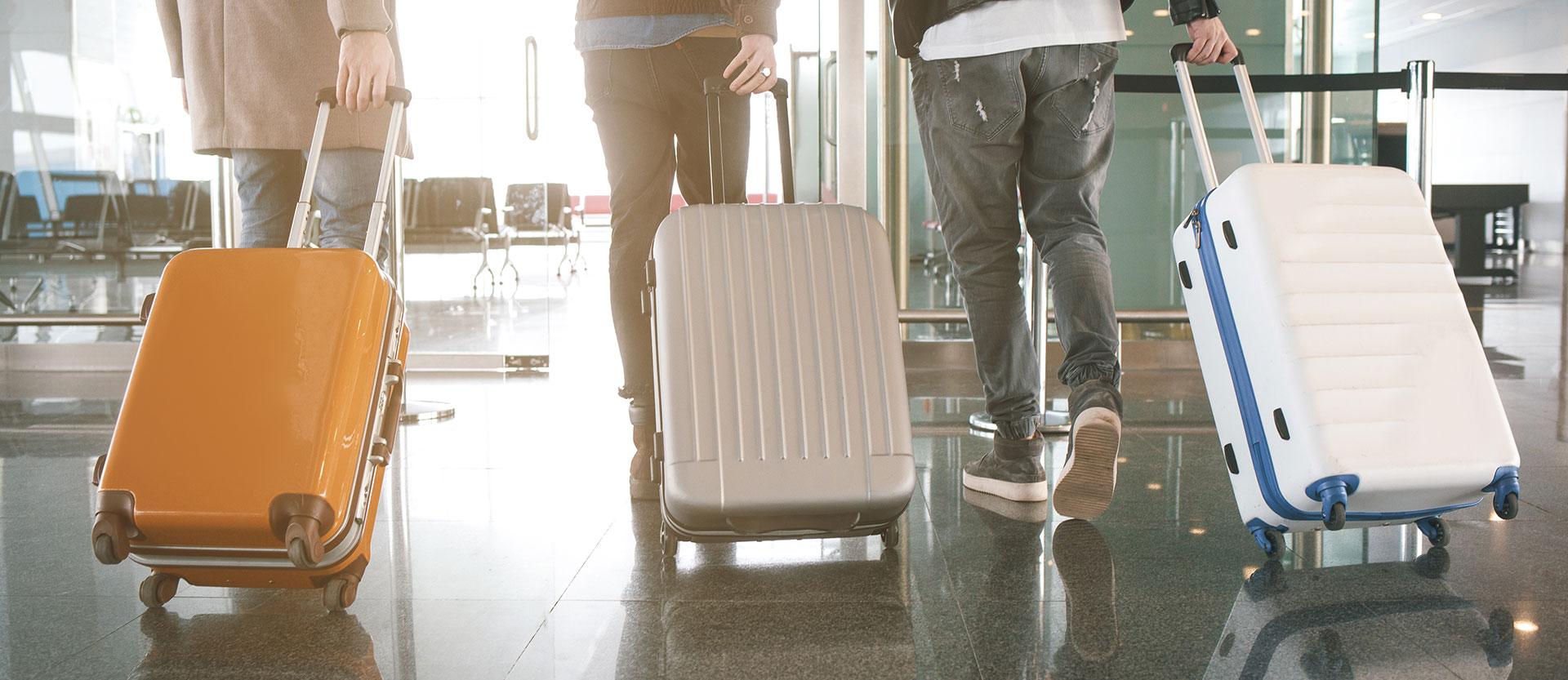 Drei Menschen mit Koffer am Flughafen